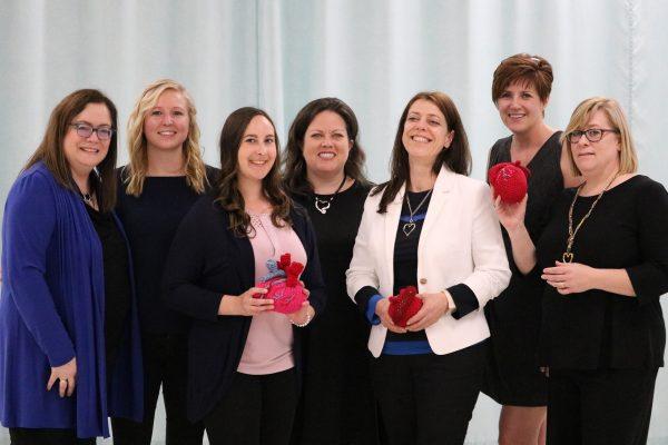 7 women holding crochet hearts